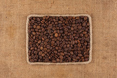 Frame made of rope with coffee beans on sackcloth, view from above. With place for your text Stock Photo