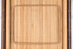Frame made of rope lies on a bamboo rug with wrapped edges. Royalty Free Stock Images
