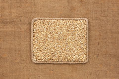 Frame made of rope with pearl barley grains on sackcloth Royalty Free Stock Photography