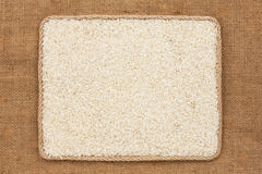 Frame made of rope with rice grains on sackcloth Stock Photo