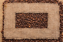 Frame made of rough burlap lies on coffee beans. As background Stock Images