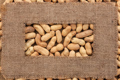 Frame made of rough burlap lies on peanuts. As background Stock Images