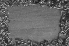 Frame made of screws on a desk. Frame made of screws, bolts on a desk ready for repair something in black and white Royalty Free Stock Photos