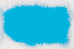 Frame made of snow on blue background Royalty Free Stock Photos