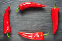 Frame made of sweet red Kapia peppers on a dark shale Royalty Free Stock Photos