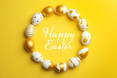 Frame made of traditional Easter eggs decorated with golden paint on color background, top view stock photography