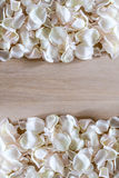 Frame made of white rose petals on wooden background with space for your text. Royalty Free Stock Photos