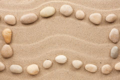 Frame made of white stones on a wavy sand. As background stock images