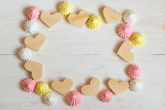 Frame made of wooden hearts and meringue pastel colors on a whit Stock Photos