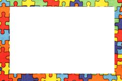 Frame of colorful puzzle pieces on cotton dyed fabric Stock Photos