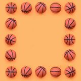 Frame of a many small orange balls for basketball sport game lies on texture background of fashion pastel orange color paper in. Minimal concept stock image