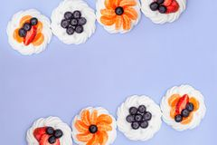 Frame of meringue with blueberries, strawberries and tangerines on a lavender background. Top view royalty free stock photography