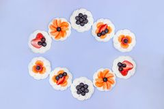 Frame of meringue with blueberries, strawberries and tangerines on a lavender background. Top view stock images