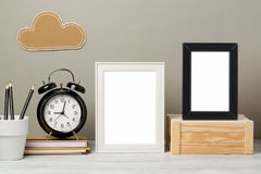 Frame mock up on table. White and black frame mock up with pencil and alarm clock. Modern stylish interior background for social media and marketing Stock Photo
