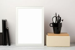 Frame mock up on table. White frame mock up with pencil and notebook. Modern stylish interior background for social media and marketing Royalty Free Stock Photo