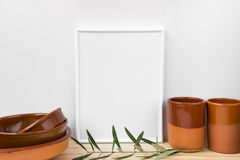 Frame mockup, collection of terracotta glazed earthenware on wood table, olive tree branch, styled image for product marketing. Online store Royalty Free Stock Photos