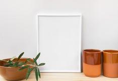 Frame mockup, earthenware glazed crockery, olive tree branch on white background, styled image for social media. Product marketing, branding Stock Photography