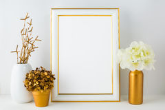 Frame mockup with ivory hydrangea in the  golden vase, white vas. E and golden flower pot. Poster white frame mockup. Empty white frame mockup for presentation Stock Photography