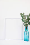 Frame mockup on white background, green eucalyptus branch in blue glass bottle, copyspace for text Stock Photography