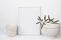 Frame mockup on white background, olive tree branch, vintage ceramic bowls, mug, copyspace for text. Styled image for social media, marketing Royalty Free Stock Images