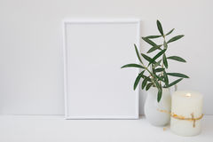 Frame mockup on white background, olive tree branches in ceramic pitcher, candle, styled image Royalty Free Stock Photos
