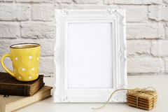 Frame Mockup. White Frame Mock Up. Yellow Cup Of Coffee With White Dots, Cappuccino, Latte, Old Books, Cookies. Display Mock-Up Stock Photo