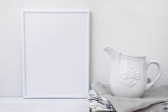 Frame mockup, white vintage pitcher on stack of linen towels, minimalist clean styled image