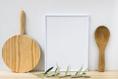 Frame mockup, wood cutting board, spoon, olive tree branch on white background, styled image
