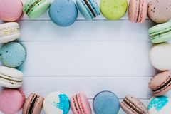 Frame of multicolored macaroons or macaron on a white wooden background, almond cookies in the form of decoration, copy. Space Stock Images