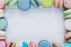 Frame of multicolored macaroons or macaron on a white wooden background, copy space.  Royalty Free Stock Photo