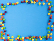 Frame of multicolored small candie on blue background. Copy space for text. Flat lay. Top view Stock Image