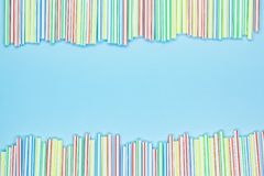 Frame of multicolored striped plastic straws on a blue background with copy space. Recycling waste stock image