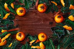 Frame with fir tree branches, tangerines, cones, and spices Royalty Free Stock Photos