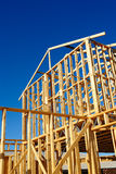 Frame of a new home. New residential construction house framing against a blue sky stock photography