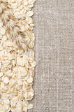 Frame oatmeal and wheat ear on burlap background Stock Images