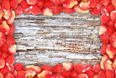 Frame Of Wild Strawberries On The Background Texture Of Wood. Stock Image