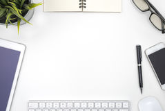Frame with office equipment on white desk. With copy space, flat lay style Stock Photography