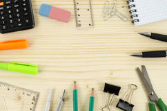 Frame of office tools on wooden table. Office tools with empty space in the middle Stock Image