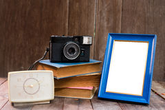 Frame with old books and old camera on wood table Stock Photos