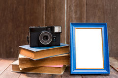 Frame with old books and old camera on wood table Stock Images