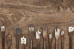Frame from old metal spade bits for drilling wood, lies wooden background. View from above. Stock Photography