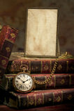Frame with old photo paper, pocket watch and books stock image