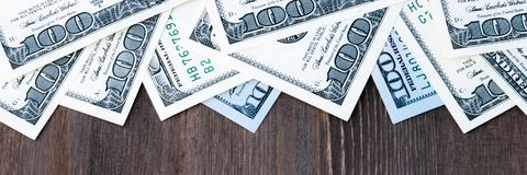 A frame of one hundred dollar bills at the top and a background of dark wood. royalty free stock images