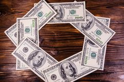 Frame of one hundred dollars bills on wooden table. Top view Stock Photo