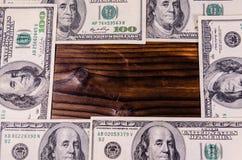 Frame of one hundred dollars bills on wooden table. Top view. Frame of the one hundred dollars bills on rustic wooden table. Top view Stock Photos