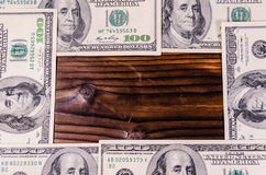 Frame of one hundred dollars bills on wooden table. Top view. Frame of the one hundred dollars bills on rustic wooden table. Top view Royalty Free Stock Photography