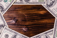 Frame of one hundred dollars bills on wooden table. Top view. Frame of the one hundred dollars bills on rustic wooden table. Top view Stock Photo