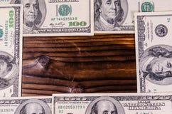 Frame of one hundred dollars bills on wooden table. Top view. Frame of the one hundred dollars bills on rustic wooden table. Top view Royalty Free Stock Photos