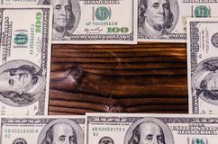 Frame of one hundred dollars bills on wooden table. Top view Royalty Free Stock Images