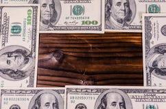 Frame of one hundred dollars bills on wooden table. Top view. Frame of the one hundred dollars bills on rustic wooden table. Top view Royalty Free Stock Images
